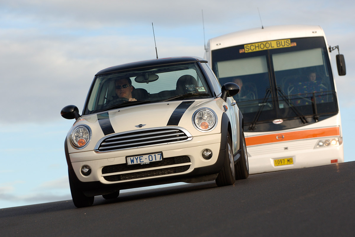 Mini Cooper driving in front of School bus on Mount Panorama Rd.